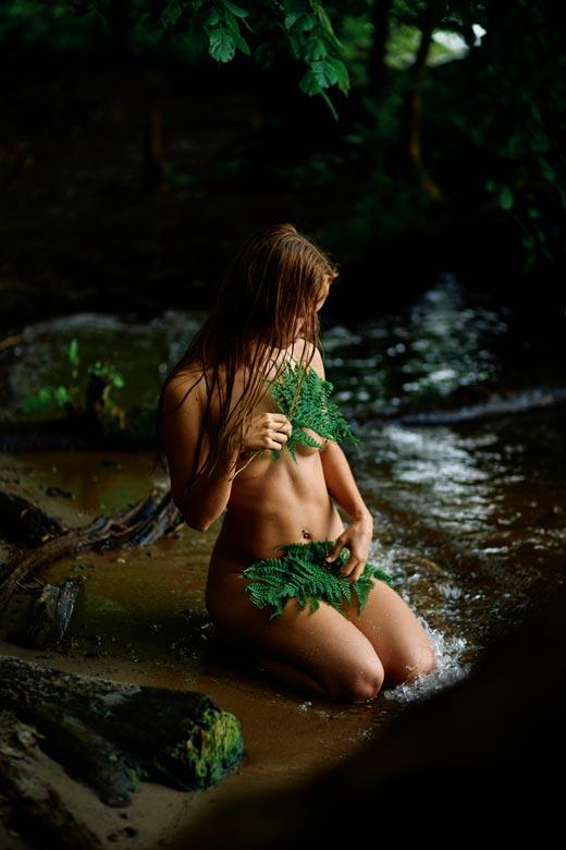 Frau mit Farn am Wasser