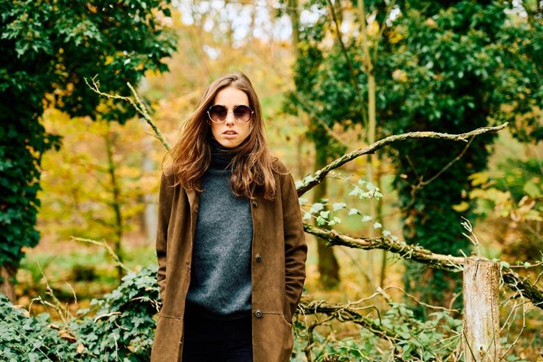 Frau mit Sonnenbrille und Ledermantel